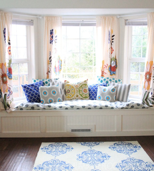 Th beautiful window seat with cushions also bay window area rug and wooden flooring for family room